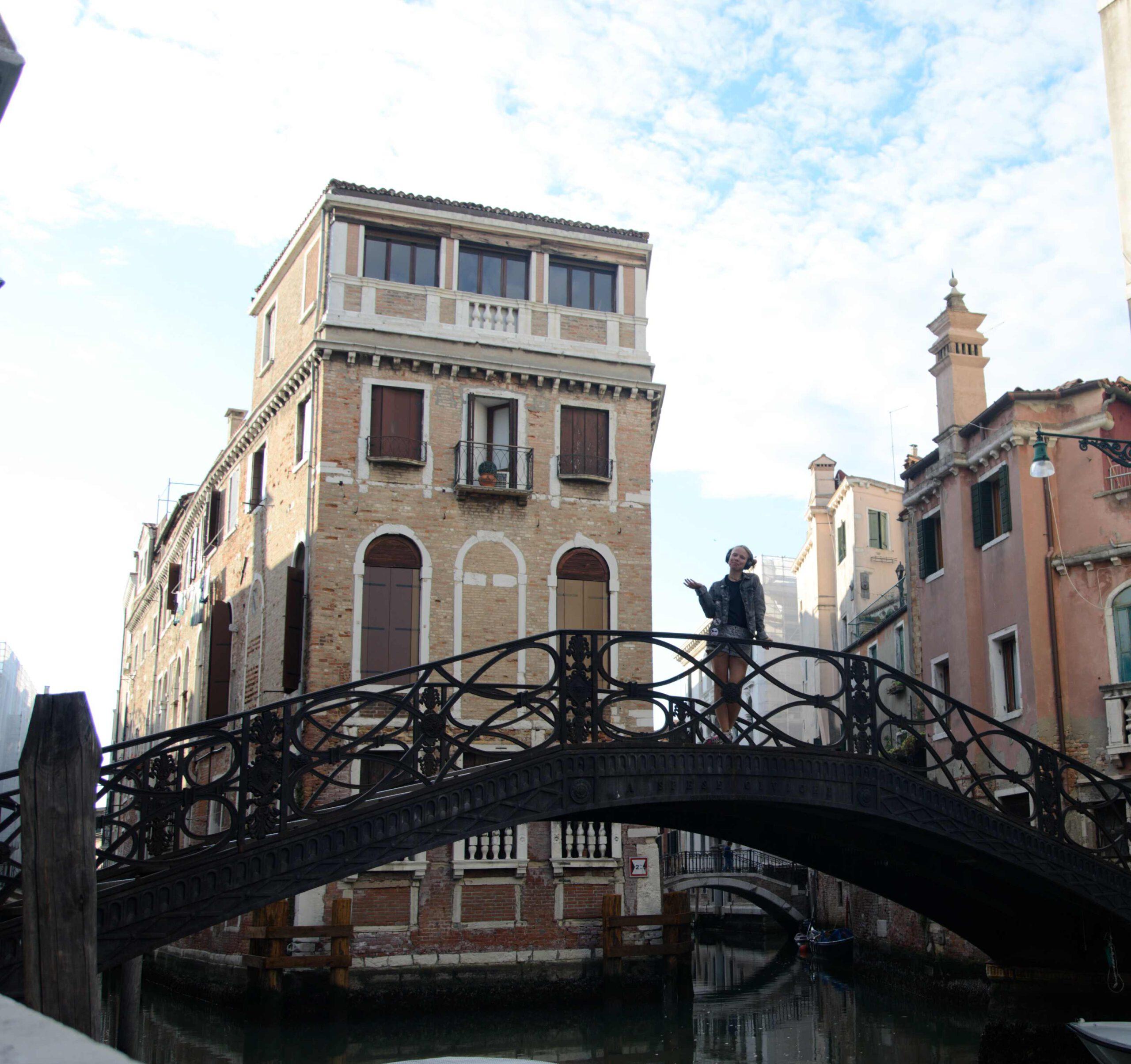 Eine Frau steht auf einer Brücke über einem Kanal in Venedig