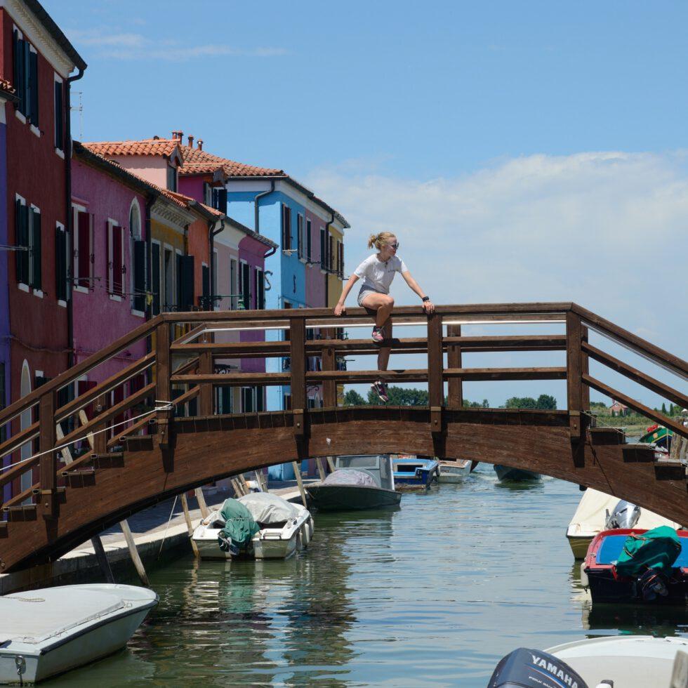 Die Boote und bunten Häuser von Burano, Venedig im Hintergrund, eine Frau klettert auf eine Holzbrücke