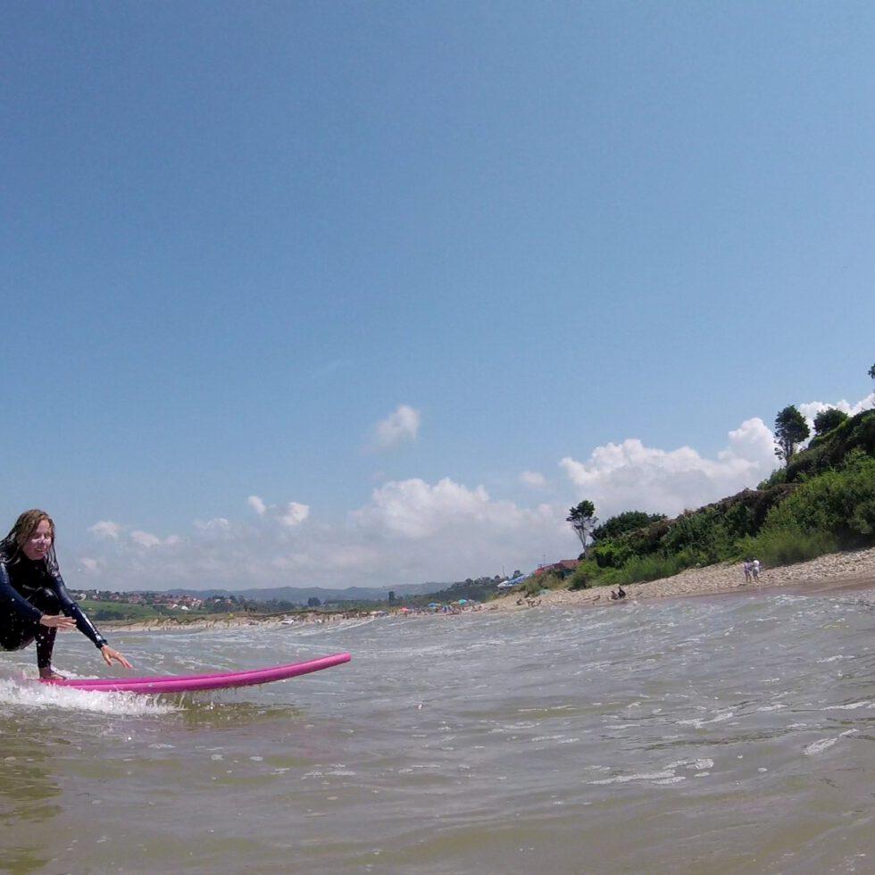 Eine Frau auf einem pinken Surfboard auf einer kleinen Welle...schon fast wieder am Strand