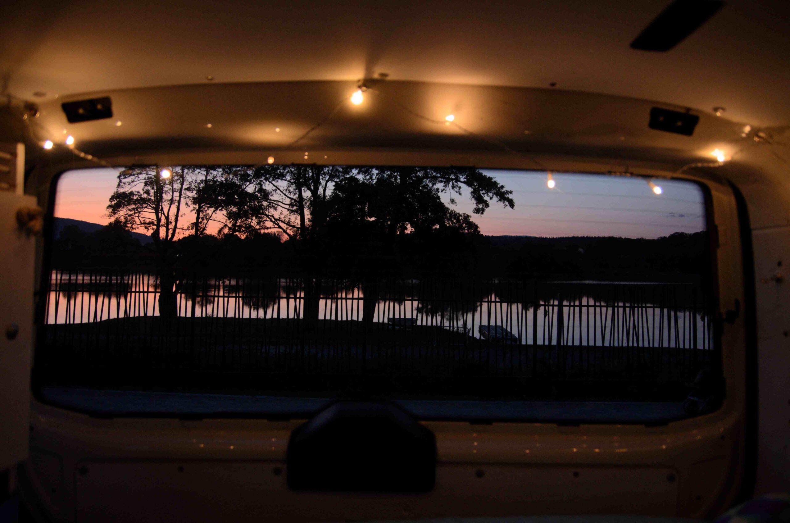 Der Sonnenuntergang hinger einem See, fotografiert durch die Heckscheibe von Tiffy mit einer Lichterkette als Deko
