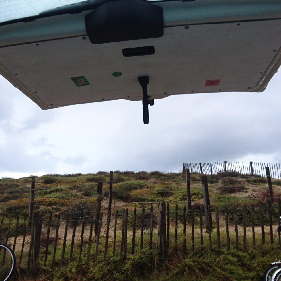 Die Heckklappe eines Bullis steht offen und man sieht die moosigen Dühnen Südfrankreichs